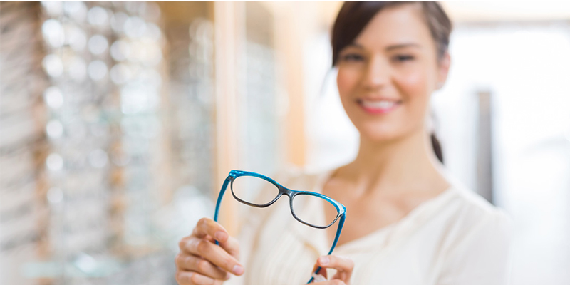Young lady holding blue eyeglasses