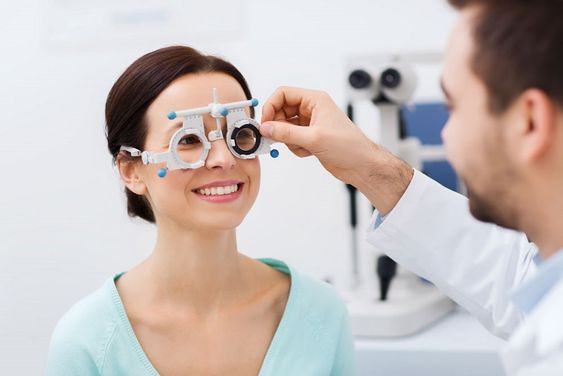 Young lady wearing trial frames and undergoing an eye test
