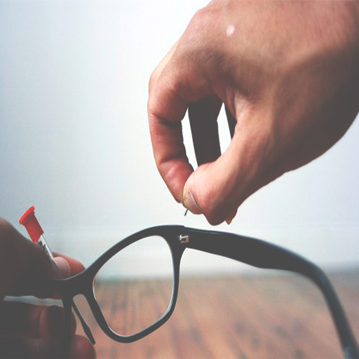 Man's hand holding black eyeglasses and a screwdriver in one hand and inserting a screw in the other hand