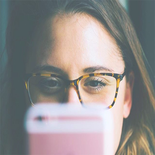A close up of a girl wearing eyeglasses looking to her pink phone