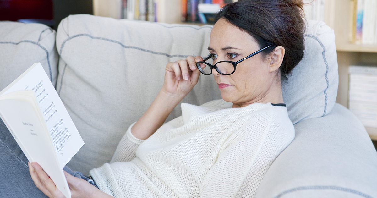 mid aged woman sitting on a sofa, holding a book in her left hand and adjusting near glasses to read