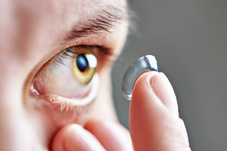 Woman holding soft contact lens on her finger and trying to wear lenses